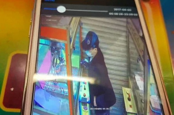 男子以玻璃擊破器的尖銳物破壞娃娃機玻璃,隨即竊取機內藍芽喇叭。(記者陳薏云翻攝)