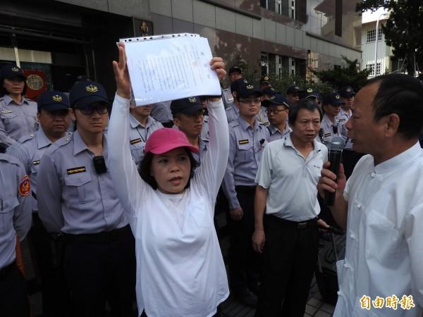 鎮代何惠娟高舉民眾的陳情書,要求鎮長周義雄接下。(記者佟振國攝)