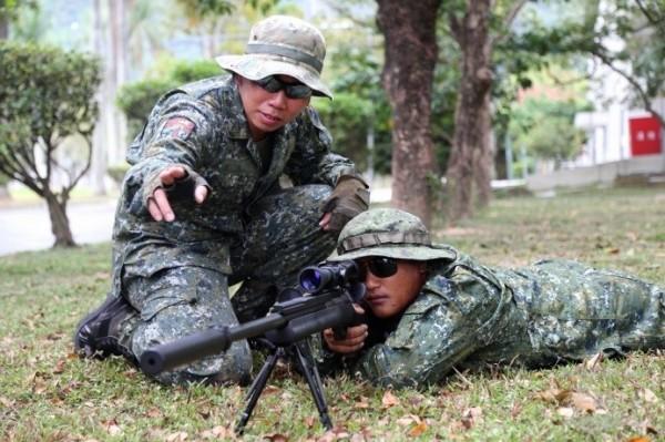 退伍狙擊手也回部隊擔任週末戰士。圖為在民國100年退伍的吳文吉(右,持槍瞄準者),自願返回部隊參與訓練。(軍聞社提供)