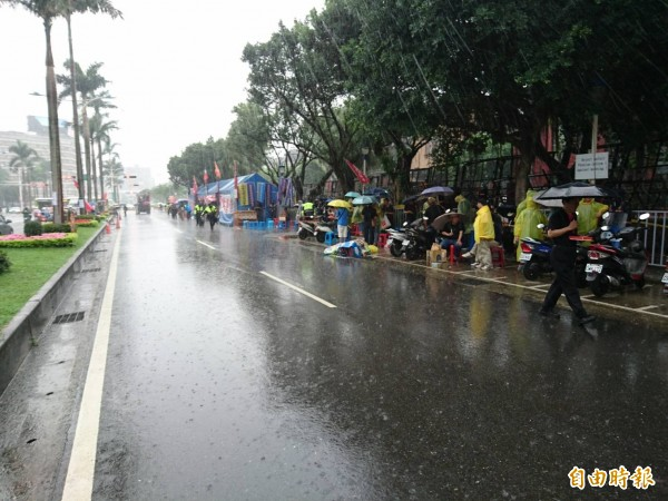 大雨中,立院大門前中山南路上的抗議現場人數零零落落。(記者王冠仁攝)