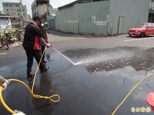 北港清潔隊員以強力水柱清除黏在路面的糖果。(記者陳燦坤攝)