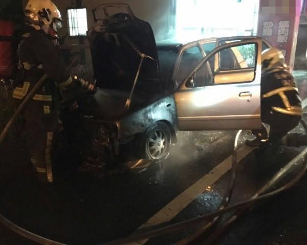 吳男使用的車子遭縱火,消防人員出水灌救。(記者陳建志翻攝)