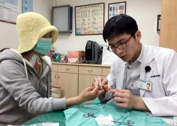 光田醫院骨科醫師楊鎮源為古婦被咬斷後接回的中指進行拆線。(光田醫院提供)