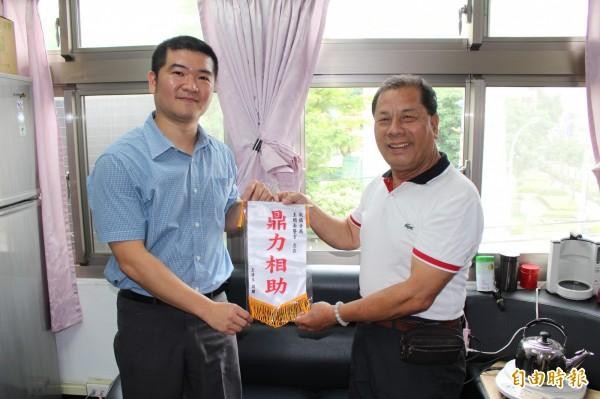 王姓男子(右)製作錦旗、獎座,感謝新北市板橋警分局尋人高手王閔南(左),幫助他找回老父親。(記者吳仁捷攝)
