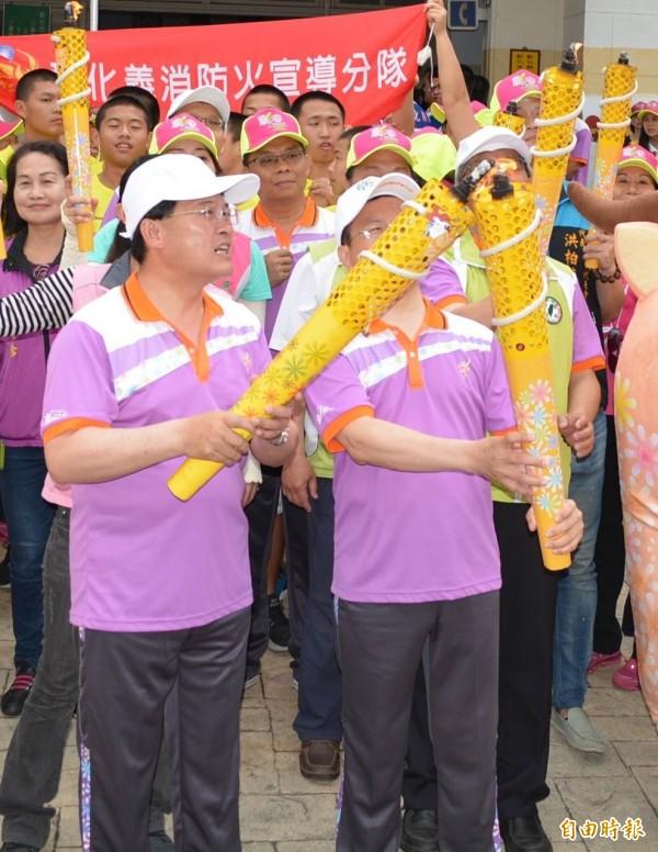 邱建富(左)以聖火幫忙將魏明谷(右)手中已熄滅的聖火點燃,引起外界不同解讀。(記者湯世名攝)