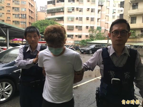 通緝犯游男(中)搭乘友人的轎車,結果因為有人違規停車被警方逮捕。(記者邱奕統攝)