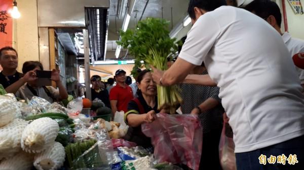 前總統馬英九今早到陳樹菊菜攤採買,要送都蘭書屋,手上拿的是芹菜,要小朋友吃了勤勞。(記者黃明堂攝)