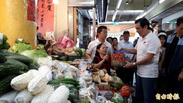 前總統馬英九今早到陳樹菊菜攤採買,陳樹菊送一箱艷荔給馬英九。(記者黃明堂攝)