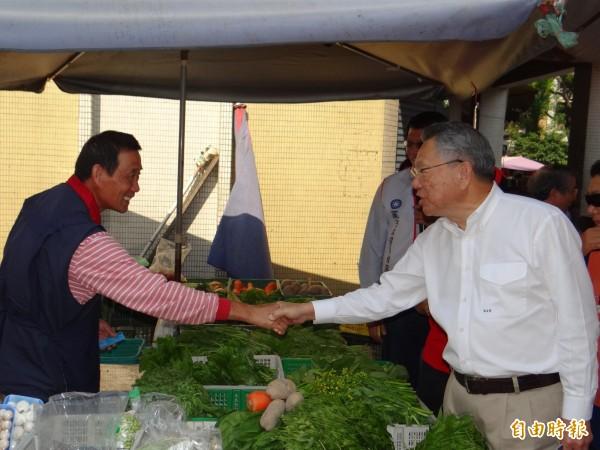 國民黨主席候選人詹啟賢(前右)到南市東區崇誨市場拜票、緊握每雙手尋求支持。(記者王俊忠攝)