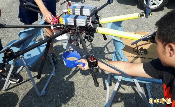 無人機研發團隊在無人機裝上自動投餌器及飼料,進行測試。(記者蔡文居攝)
