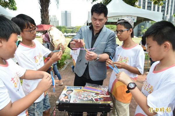街頭藝人魔術表演教學,深受青少年喜愛。(記者張忠義攝)