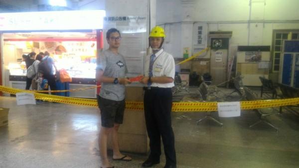 台南火車站長徐竹平送壓驚紅包給遭火車站天花板砸傷的吳姓男大學生(前左)。(記者王俊忠翻攝)