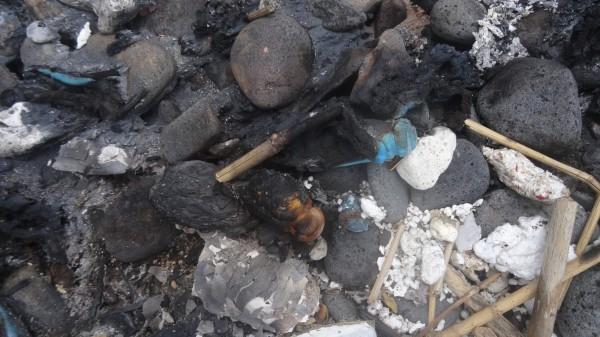 部分海漂物未燃燒完全,還留在現場的垃圾。(記者劉禹慶翻攝)