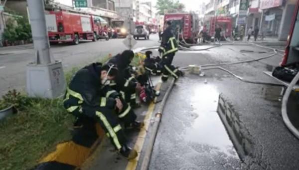 2天2夜的搏鬥,消防人員累倒癱在馬路分隔島上休息。(翻攝畫面)