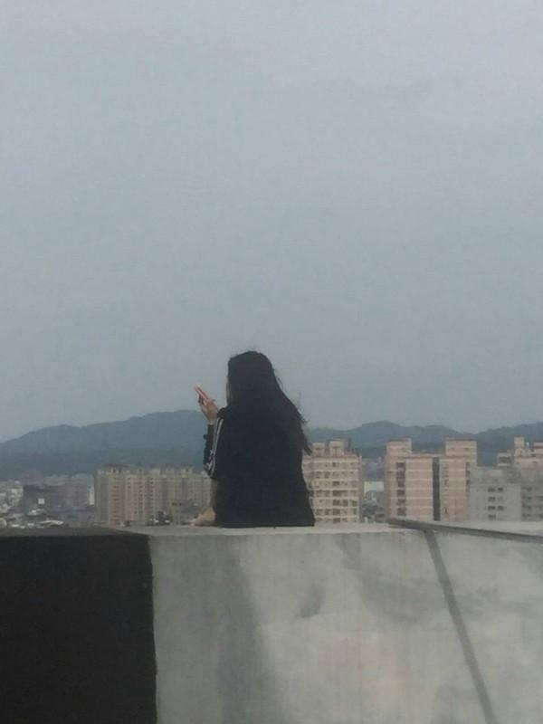 吳女枯坐12樓高牆有意輕生,被警消人員及時救下。(記者鄭淑婷翻攝)