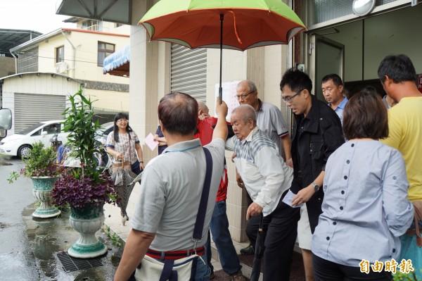 老伯伯冒雨拄著拐杖,一早就到雲林縣黨部投票。(記者詹士弘攝)