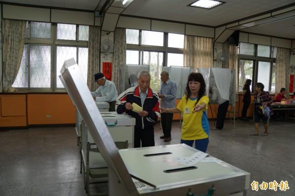 不少資深黨員冒雨前來投票。(記者詹士弘攝)