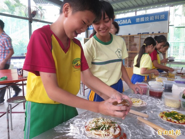 水里郡坑國小師生們跟著廚師將梅果、過貓野菜放進餅皮,親手製作特殊的梅子披薩。(記者劉濱銓攝)