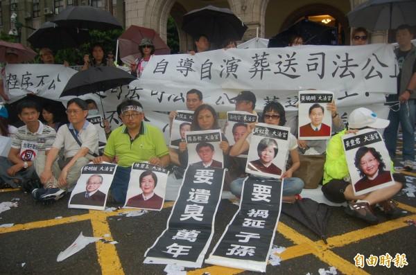 反同團體不滿釋憲案結果,傍晚時雨中靜坐抗議。(記者楊國文攝)