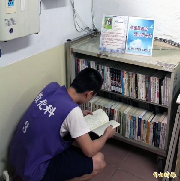 基隆監獄收容人幫忙抬書,將書籍上架後,迫不急待的閱讀。(記者俞肇福攝)