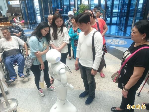 童綜合醫院引進機器人提供醫藥查詢等服務,吸引民眾上前互動。(記者歐素美攝)