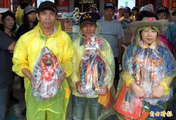 台江青春伴行,鄉親奉請神明穿上雨衣一路陪行。(記者蔡文居攝)
