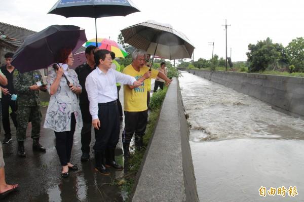 溪州鄉長黃盛祿(黃衣者)指出,三號圳排水溢堤,才會造成榮光村淹水。(記者陳冠備攝)