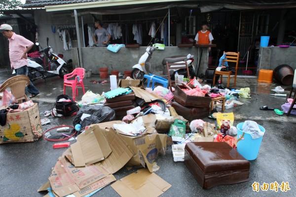 榮光村居民趁水位一退,趕緊把泡水家當清出。(記者陳冠備攝)