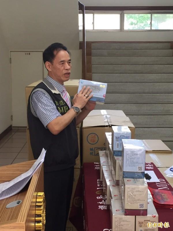 南投縣調查站副主任李金山,出示冒充台灣茶比賽的越南茶。(記者陳鳳麗攝)