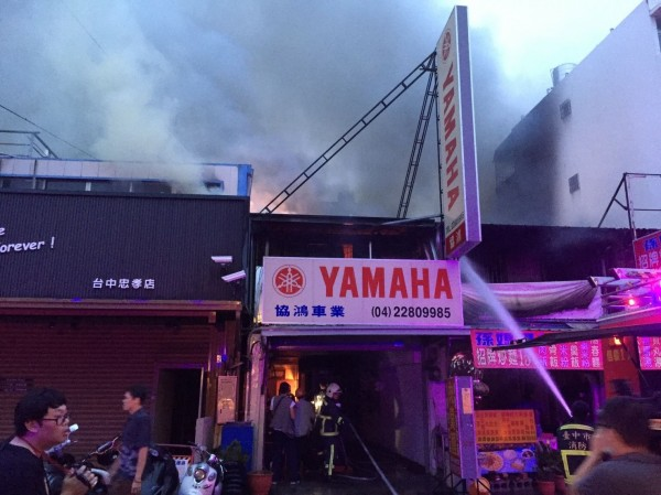 現場火勢猛烈濃煙不斷竄出,消防人員急拉水線灌救。(記者許國楨翻攝)