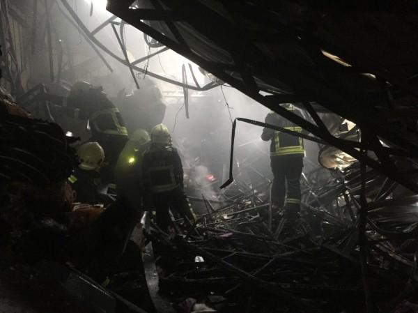 消防人員進入火場,在燒到塌陷的鐵皮建築下發現一對母女焦屍。(記者許國楨翻攝)