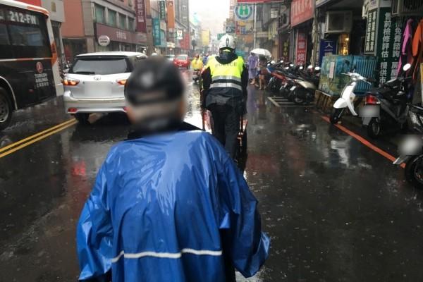 警員冒雨將推車推至安全處。(記者曾健銘翻攝)