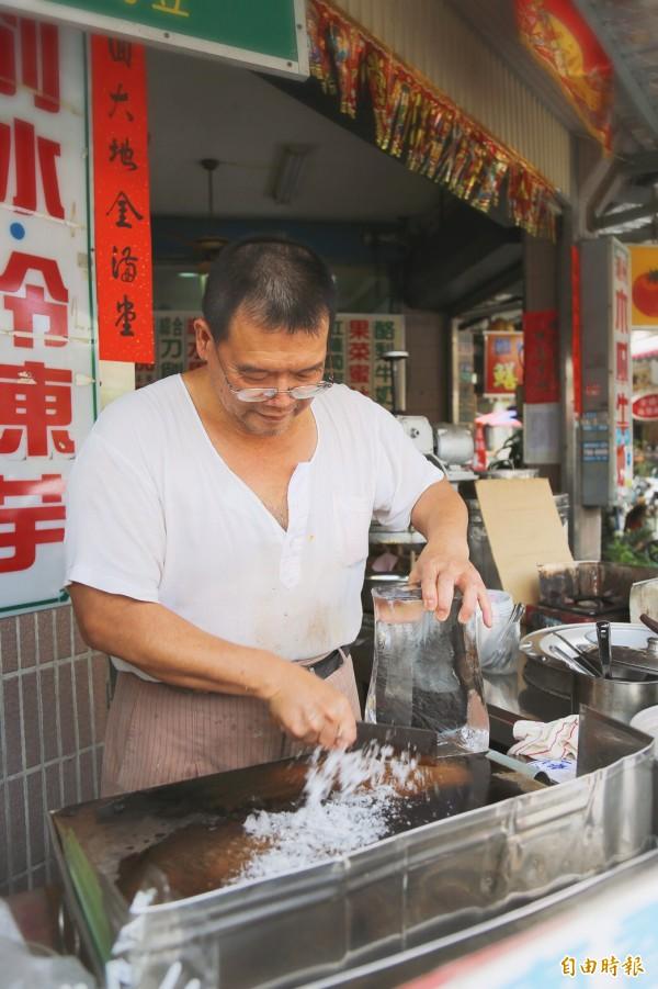 老闆張金泉一手扶著冰磚,一手拿起菜刀由上往下快速削動。(記者邱芷柔攝)