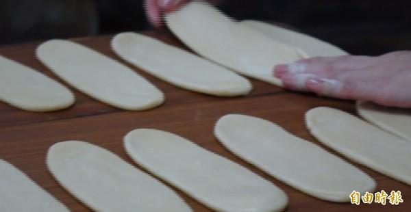 鹿港兔仔寮明豐珍牛舌餅製作,把餅皮包餡壓平後,再用手拉一拉,讓大小能夠平均。(記者劉曉欣攝)