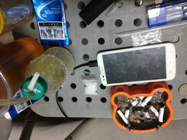 警方在鐵皮屋內的桌上,查獲安非他命毒品、吸食器、毒咖啡包等證物。(記者黃良傑翻攝)