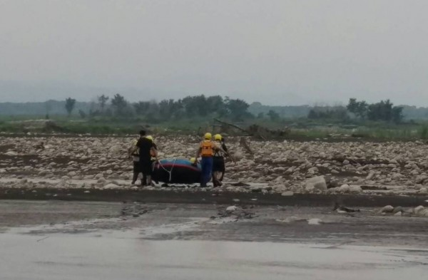 濁水溪溪州鄉榮光村段河床沙洲發現無名屍,警方及消防人員出動橡皮艇載運遺體。(記者陳冠備翻攝)