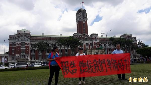 許耿睿及屏東縣議員蔣月惠,在總統府前拉紅布條寫著「報告總統,我們準備好了」。(記者蔡宗憲翻攝)