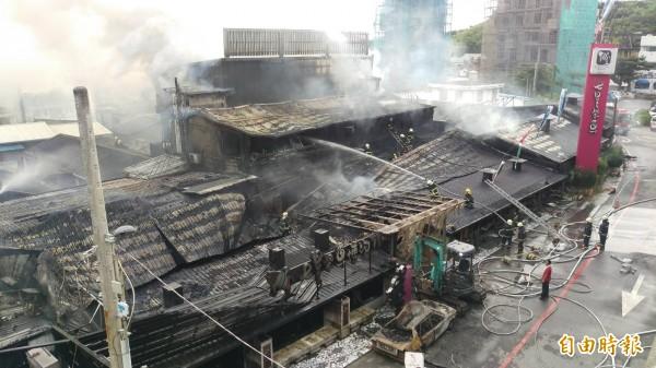 清晨天色微亮,消防人員進行最後殘火撲滅,占地500坪的博物館已付之一炬,僅留存聳立在一旁的「七星柴魚博物館」招牌無恙。(記者王峻祺攝)