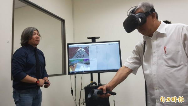 新竹縣長邱鏡淳(右)在中國科技大學的ACE基地,用VR體驗內灣國小互動繪本,大開眼界。(記者廖雪茹攝)