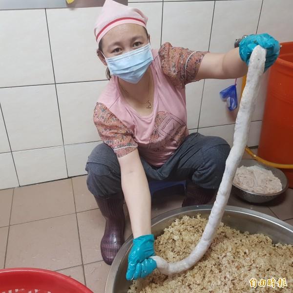 員工將攪拌過紅蔥頭、油蔥與豬油等秘方的糯米飯,用人工灌入大腸圈內。(記者俞肇福攝)