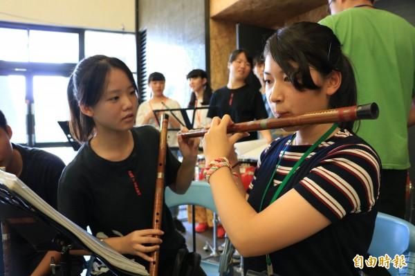 新藝高學生(左)教日本學生吹奏中國笛。(記者曾迺強攝)