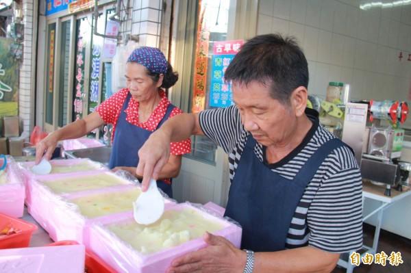 蔡候跟妻子何秀鳳,用飯匙把冰裝入保麗龍盒裡,壓到沒有縫隙,增加保溫。(記者陳冠備攝)