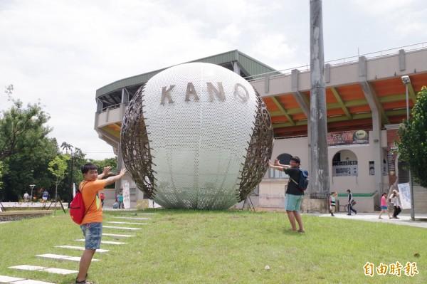 嘉義市立棒球場前KANO巨球,透過借位方式拍照,遊客宛如在推球。(記者王善嬿攝)