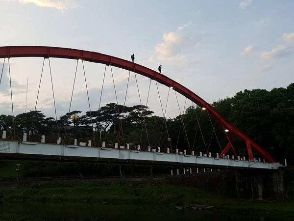 2人爬上拱橋頂端的危險行徑,全被路過民眾拍下。(民眾范才達提供)