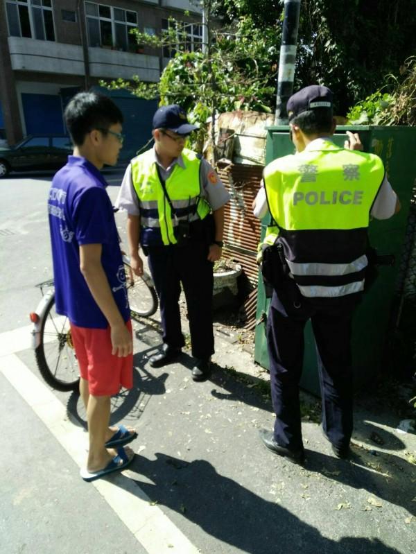 警方開啟舊衣回收箱,協助潘子找尋父親的私房錢。(記者陳賢義翻攝)