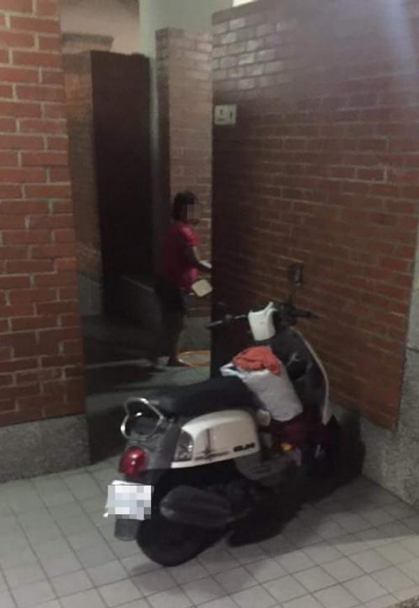 網友拍下,1輛機車停放在扶輪公園公廁前,機車腳踏板上,擺放著一大袋衣物,1名婦女正要進入公廁,疑似利用公廁洗手台清洗衣服。(取自臉書「竹南大小事!」)