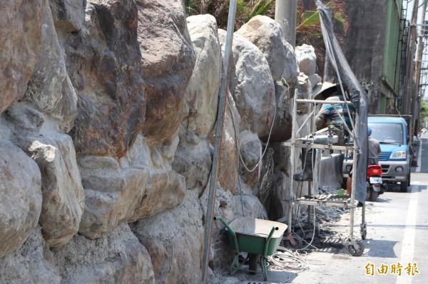 業者最近正在將巨石圍牆的石頭突出占用道路用地的部分磨平。(記者林敬倫攝)