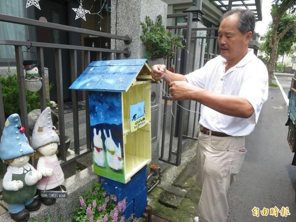 集集鎮在地社區發起漂書計畫,漂書發起人胡堯儲忙著固定漂書書箱,盼能提升小鎮閱讀風氣。(記者劉濱銓攝)