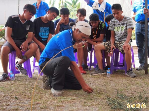 池上阿美族青年認真看著老師學做陷阱。(記者王秀亭攝)