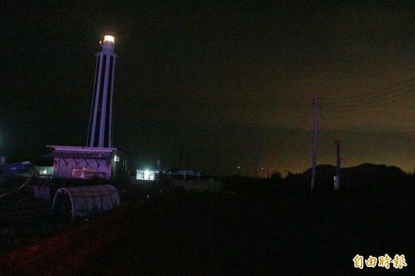 王功漁港入夜後幾乎伸手不見五指,只剩遠處燈塔釋放微弱燈光。(記者陳冠備攝)